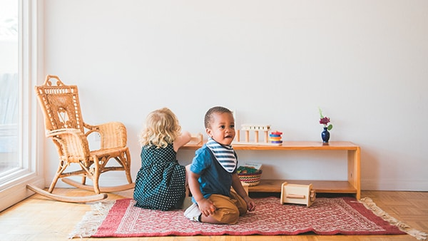 Two children interacting with Montessori materials at Your Parenting Mentor home